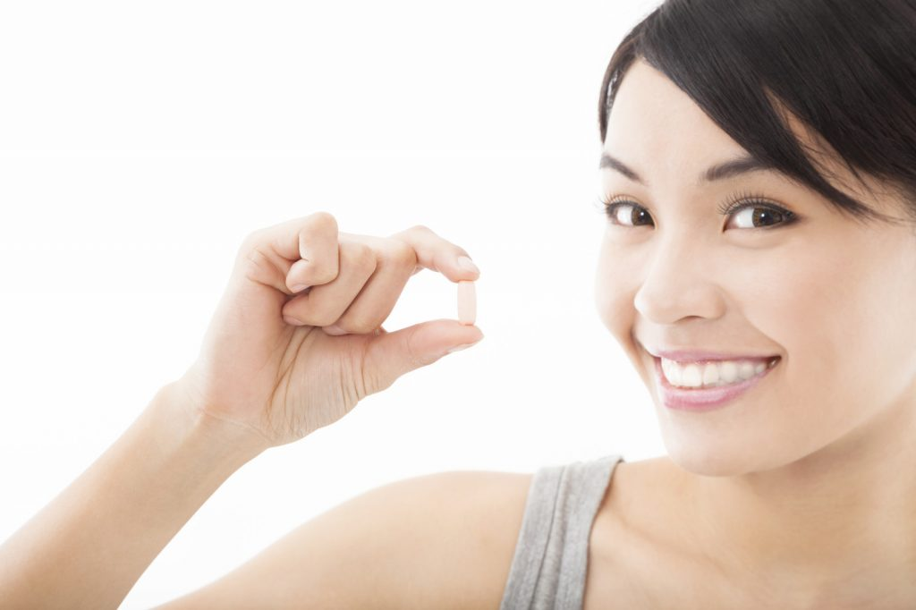 smiling woman holding pill of high supplement quality