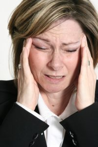 woman with migraine headache who needs a chiropractor
