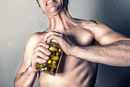 man straining to open pickle jar with prominent tendons made from collagen