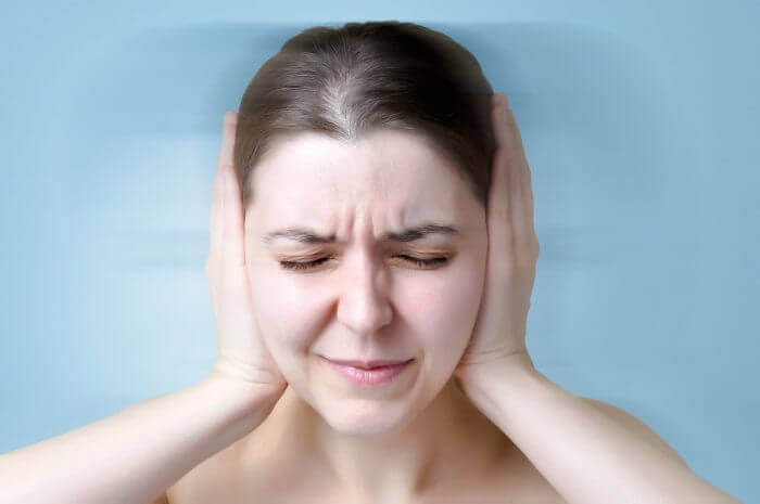 woman with tinnitus holding her ears to make the ringing stop or get rid of tinnitus